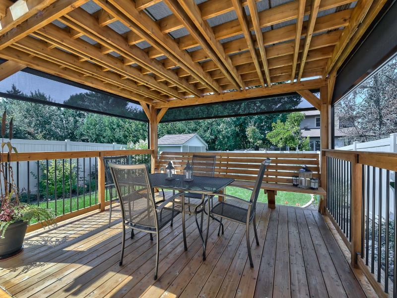 under wooden pergola with screens